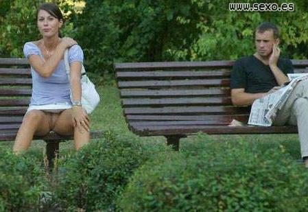 una guarrita provocando enseña el coño en un banco sentada